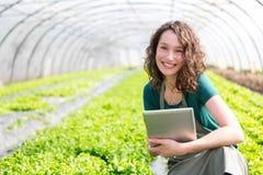 Ritratto di un agricoltore attraente in una serra facendo uso della compressa Immagini Stock