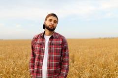 Ritratto di un agricoltore barbuto che sta in un giacimento di grano Uomo dei pantaloni a vita bassa di Stilish con il cappello d Fotografia Stock Libera da Diritti