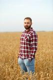 Ritratto di un agricoltore barbuto che sta in un giacimento di grano Uomo dei pantaloni a vita bassa di Stilish con il cappello d Fotografie Stock Libere da Diritti