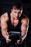 Ritratto di un allenamento bello dell'uomo su forma fisica il buio della bici di esercizio alla palestra Fotografie Stock Libere da Diritti