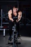 Ritratto di un allenamento bello dell'uomo su forma fisica il buio della bici di esercizio alla palestra Immagini Stock