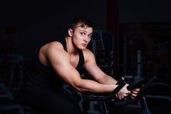 Ritratto di un allenamento bello dell'uomo su forma fisica il buio della bici di esercizio alla palestra Fotografia Stock Libera da Diritti
