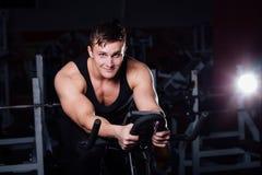 Ritratto di un allenamento bello dell'uomo su forma fisica il buio della bici di esercizio alla palestra Fotografie Stock