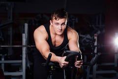 Ritratto di un allenamento bello dell'uomo su forma fisica il buio della bici di esercizio alla palestra Immagine Stock