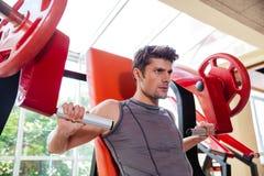 Ritratto di un allenamento del culturista sulla macchina di forma fisica alla palestra Fotografia Stock Libera da Diritti