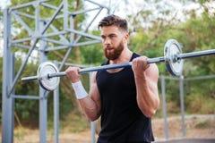 Ritratto di un allenamento muscolare dell'uomo con il bilanciere Fotografia Stock