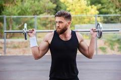 Ritratto di un allenamento muscolare dell'uomo con il bilanciere Immagine Stock Libera da Diritti