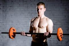 Ritratto di un allenamento muscolare dell'uomo con il bilanciere alla palestra Immagini Stock Libere da Diritti