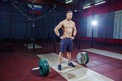 Ritratto di un allenamento muscolare dell'uomo con il bilanciere alla palestra supporti vicino alla barra, riposante Fotografia Stock