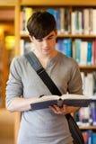 Ritratto di un allievo bello che legge un libro Immagini Stock