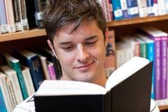 Ritratto di un allievo maschio sorridente che legge un libro Immagine Stock Libera da Diritti