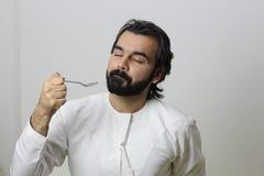 Ritratto di un arabo mangiatore di uomini con il cucchiaio e godere del gusto con i suoi occhi chiusi fotografie stock