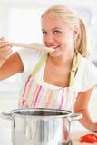 Ritratto di un assaggio biondo della donna il suo pasto Fotografia Stock