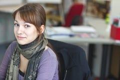 Ritratto di un astuto una giovane donna attraente in ufficio Immagini Stock Libere da Diritti