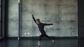 Ritratto di un ballerino di balletto maschio che balla balletto classico nello studio su un fondo scuro Movimento lento stock footage