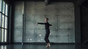 Ritratto di un ballerino di balletto maschio su un fondo scuro il ballerino sta filando sulla punta dei piedi e sta muovendosi me stock footage