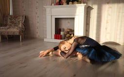 Ritratto di un ballerino di balletto professionista che si siede sul pavimento di legno alla luce del sole Concetto di balletto Fotografia Stock