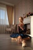 Ritratto di un ballerino di balletto professionista che si siede sul pavimento di legno Ballerina femminile che ha un resto Fotografie Stock