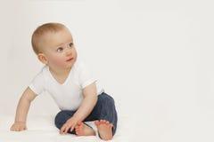 Ritratto di un bambino con gli occhi azzurri su un fondo grigio in jeans ed in una maglietta bianca fotografie stock