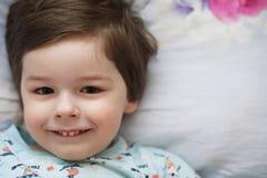 Ritratto di un bambino piccolo che si trova su un cuscino Immagine Stock Libera da Diritti