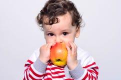 Ritratto di un bambino sveglio che mangia una mela Immagini Stock Libere da Diritti