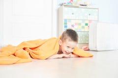 Ritratto di un bambino sveglio in plaid arancio nella casa fotografia stock libera da diritti