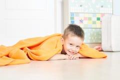 Ritratto di un bambino sveglio in plaid arancio nella casa immagine stock
