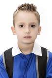 Ritratto di un bambino in uniforme scolastico e zaino Fotografie Stock Libere da Diritti