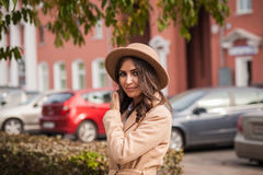 Ritratto di un cappello e di un cappotto d'uso della ragazza contro le macchine urbane del paesaggio del contesto fotografia stock