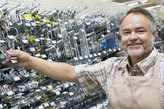Ritratto di un commesso maturo felice che tiene attrezzatura metallica in ferramenta Fotografia Stock Libera da Diritti