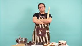Ritratto di un cuoco unico di pasticceria maschio serio con il matterello a disposizione video d archivio