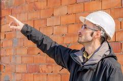 Ritratto di un elmetto protettivo d'uso dell'ingegnere al cantiere immagini stock libere da diritti