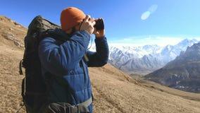 Ritratto di un fotografo barbuto felice del viaggiatore in occhiali da sole ed in un cappello con una macchina fotografica reflex stock footage