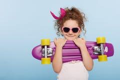 Ritratto di un fronte di divertimento di una bambina in occhiali da sole rosa, tenente pattino in mani, isolate su un fondo blu fotografia stock libera da diritti
