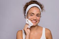 Ritratto di un fronte di pulizia della giovane donna in uno studio, in una bellezza ed in una cura di pelle fotografia stock libera da diritti