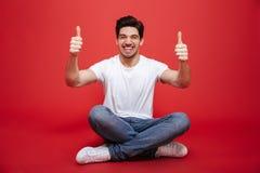 Ritratto di un giovane allegro nella seduta bianca della maglietta Immagini Stock Libere da Diritti