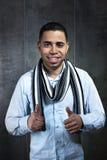 Ritratto di un giovane che mostra i pollici su in parete scura Fotografia Stock Libera da Diritti