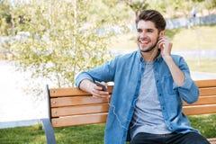Ritratto di un giovane che si siede sulla conversazione del banco Immagini Stock Libere da Diritti
