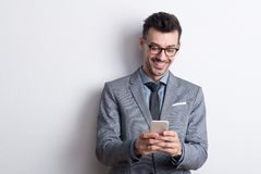 Ritratto di un giovane con lo smartphone in uno studio, invio di messaggi di testo immagini stock