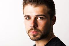 Ritratto di un giovane con una barba da 3 giorni davanti alla parte posteriore di bianco Fotografia Stock