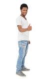 Ritratto di un giovane felice che gesturing i pollici su Fotografia Stock