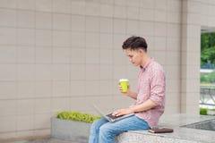 Ritratto di un giovane felice che si siede sulle scale della città con La Fotografia Stock