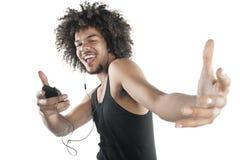 Ritratto di un giovane felice nel dancing della maglia alle arie del riproduttore mp3 sopra fondo bianco Fotografia Stock