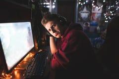 Ritratto di un giovane frustrato che gioca i video giochi a casa su un computer, esaminante una macchina fotografica con un front immagini stock
