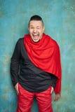 Ritratto di un giovane negli allentamenti rossi ed in una camicia nera, sciarpa rossa, sorrisi luminosi Fotografie Stock