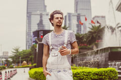 Ritratto di un giovane nello stile casuale con i grattacieli nei precedenti con il telefono a disposizione Fotografie Stock Libere da Diritti