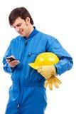 Ritratto di un giovane operaio che per mezzo del telefono cellulare Immagini Stock Libere da Diritti