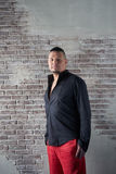 Ritratto di un giovane, paffuto, vestito negli allentamenti rossi ed in una camicia nera Fotografie Stock Libere da Diritti