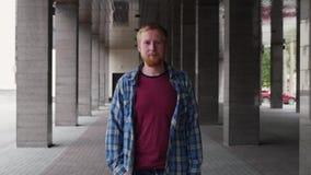 Ritratto di un giovane su un fondo delle colonne Un giovane sta sulla via accanto alla costruzione Sguardo serio video d archivio