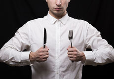 Ritratto di un giovane in una camicia bianca con un coltello e una forcella i Immagini Stock
